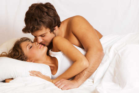 beautiful bed: Young beautiful couple kissing in bed