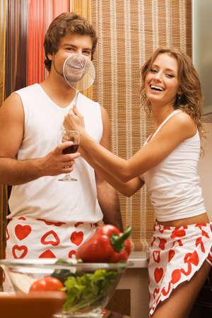 Young beautiful couple having fun in their kitchen photo