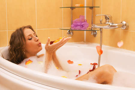 lying in bathtub: Beautiful lady taking a bath with rose petals