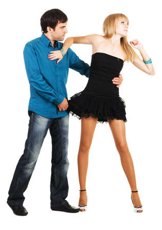 Beautiful young couple in casual clothing flirting, white background photo