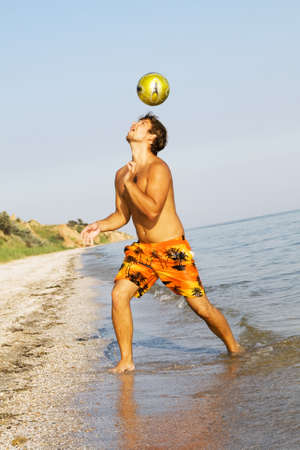 Handsome young man playing football on a sea shore photo