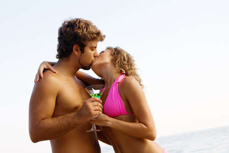Young happy couple on the seaside with cocktails is kissing photo