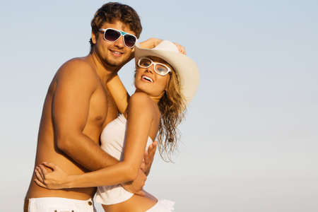 Portrait of a beautiful young couple against blue sky background photo