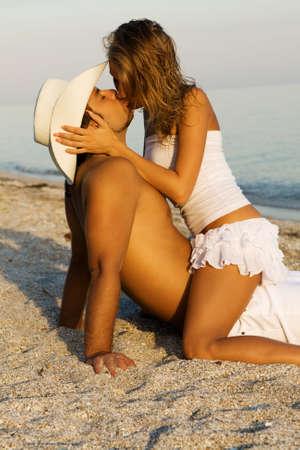 personas abrazadas: Joven pareja en elegante vestido blanco bes�ndose en la orilla del mar