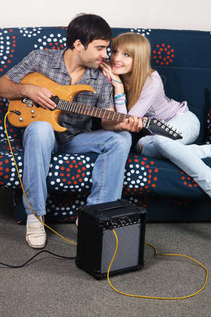 Cheerful couple resting on a sofa with electric guitar photo