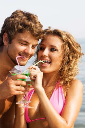 parejas jovenes: J�venes hermosas pareja en los c�cteles de beber costero