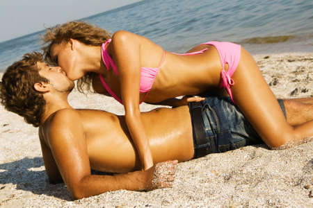 pareja besandose: Joven pareja apasionada bes�ndose en la arena  Foto de archivo