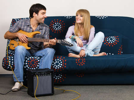 Young beautiful couple resting at home and playing electric guitar  photo