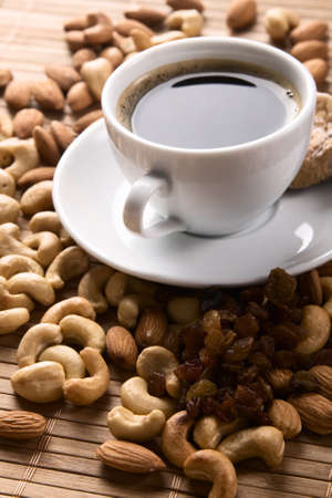 Cup of coffee with nuts, fig and raisins still life  photo