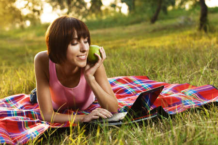 Lovely girl having a rest with laptop on picnic Stock Photo - 7805824