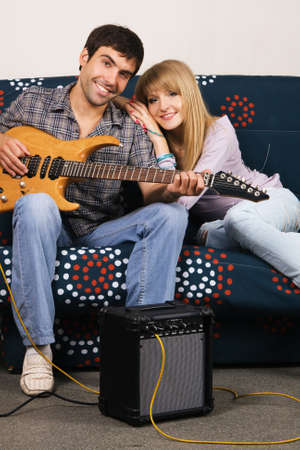 Romantic young couple resting on a sofa with a music  photo