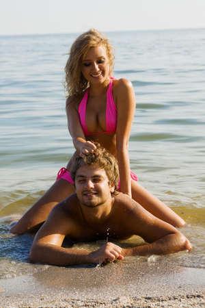 Beautiful young couple having fun on the seaside.  photo