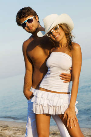 Young beautiful couple on a sea shore, focus on woman photo
