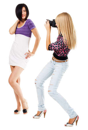 Young woman taking a picture of pretty girl, white background  photo
