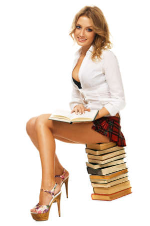 Sexy student girl with a stack of books against white background photo