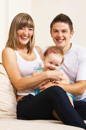 Happy young parents with their little daughter having fun at home photo