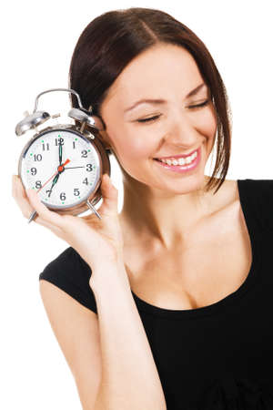 Cheerful young woman listening to the ticking of alarm clock  photo