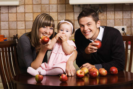 Happy young parents with their little daughter at kitchen with a lot of red apples photo
