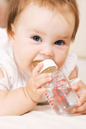 hand holding bottle: Cute baby drinking water and looking at the camera