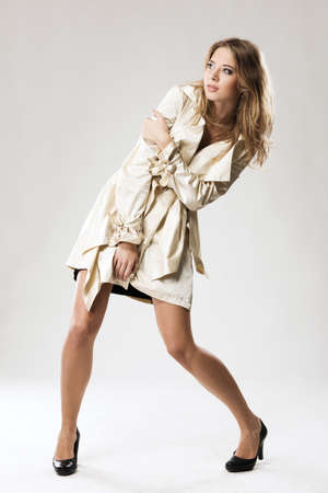 Pretty model in beige fashionable raincoat strangely posing against gray background Stock Photo - 8147070