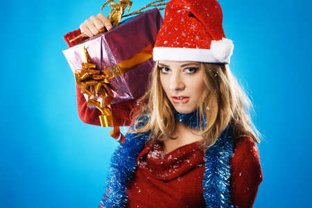 Evil Christmas girl with a gift box against blue background photo