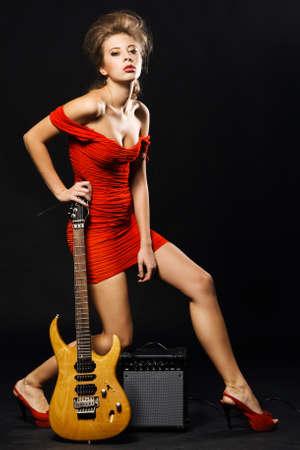 rocker girl: Modelo extravagante en un vestido rojo con la guitarra el�ctrica y amplificador
