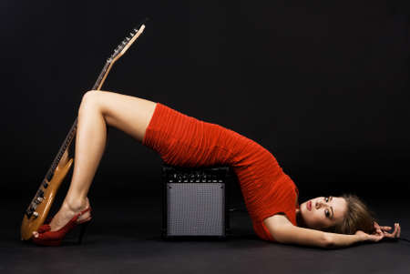 rockstar: Gorgeous model in a red dress with electric guitar and amplifier