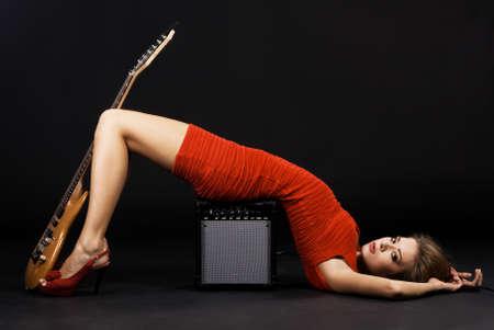 guitarra sexy: Precioso modelo en un vestido rojo con la guitarra el�ctrica y amplificador  Foto de archivo