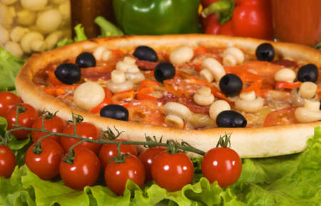 Closeup picture of a pizza with vegetables and cherry tomato photo