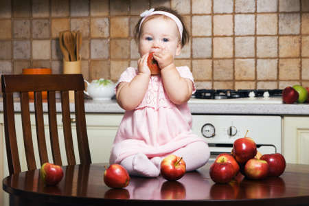 Little girl on table at kitchen eating an apple photo