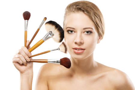 Portrait of a beautiful young woman with makeup brushes  photo