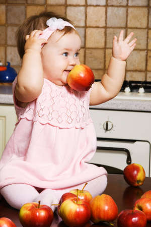 Little girl sitting on table at kitchen and playing with red apples photo
