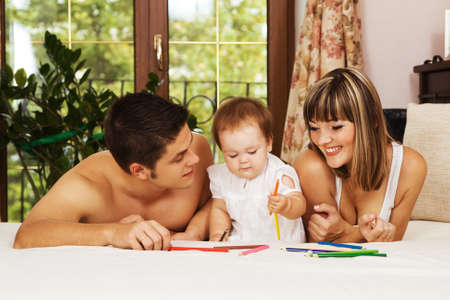 Happy parents playing with their little daughter at bedroom photo