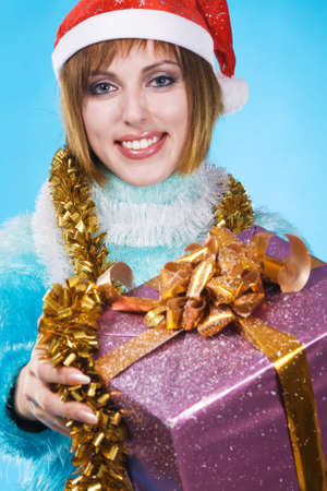Festive girl with Christmas gift against blue background photo