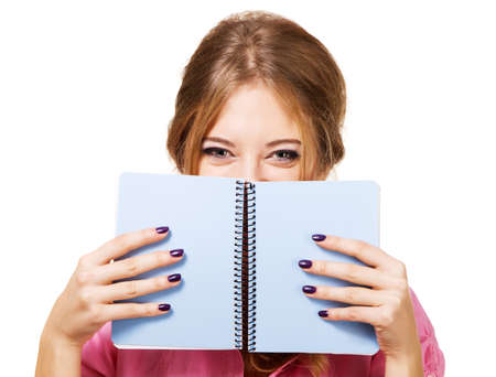 Lovely girl hiding behind notebook, white background photo