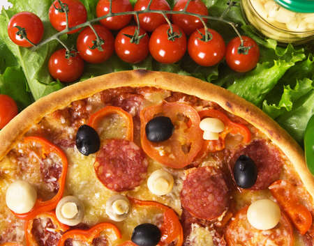 Closeup picture of a pizza with vegetables and cherry tomatoes photo