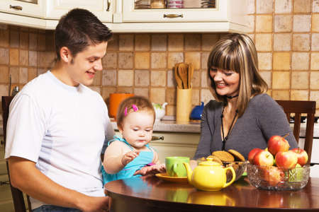 Happy young parents with their little daughter at kitchen  photo