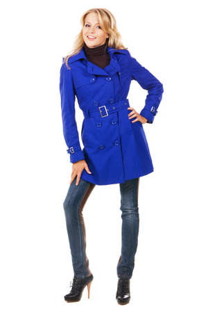 Pretty model in a blue coat against white background  photo