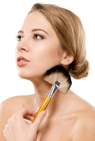 Closeup portrait of a beautiful young woman applying makeup photo