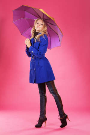 Lovely woman in a blue coat with umbrella against pink background  photo