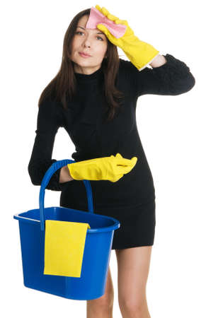 Young tired housewife in elegant dress holding a swab and bucket, white background  photo