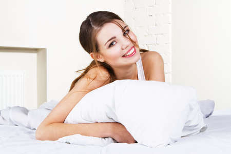 white pillow: Young beautiful woman lying in bed Stock Photo