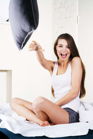 Pillow fight: Young beautiful woman throwing a pillow at camera