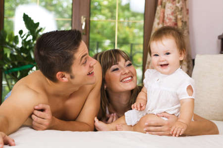Happy young parents with their little daughter having fun at home Stock Photo - 8653425