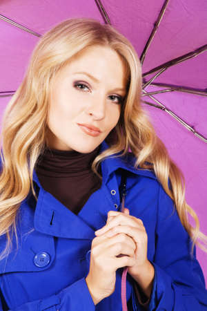 Portrait of a pretty model in blue coat holding a violet umbrella  photo
