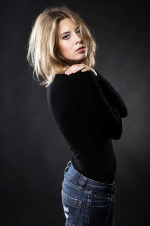 dark blond: Beautiful fashion model in stylish clothing against black background