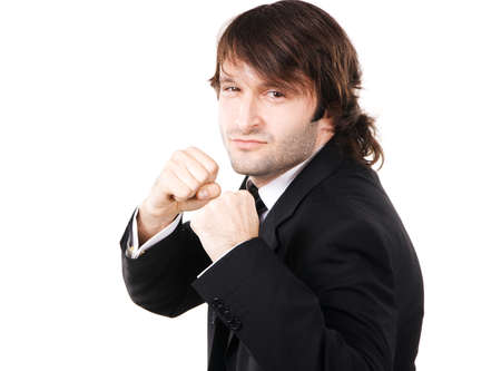 Young businessman in boxing pose, white background  photo
