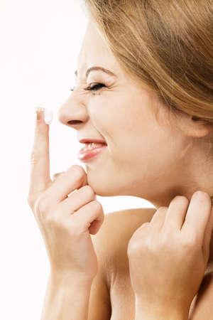 Cheerful girl apply moisturize cream, white background photo