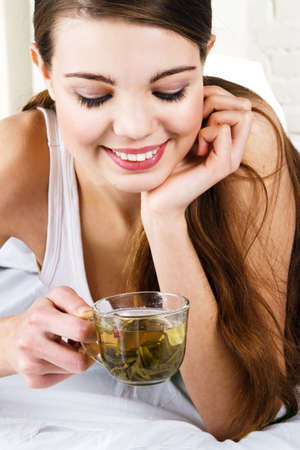 brown cup tea: Young beautiful woman drinking morning tea Stock Photo