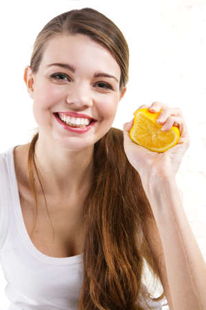 squeezing: Attractive young woman squeezing and orange, white background